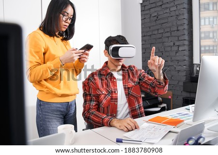 Waist up portrait of the designer gesturing while using virtual reality headset near his female colleague at the light modern office. Stock photo