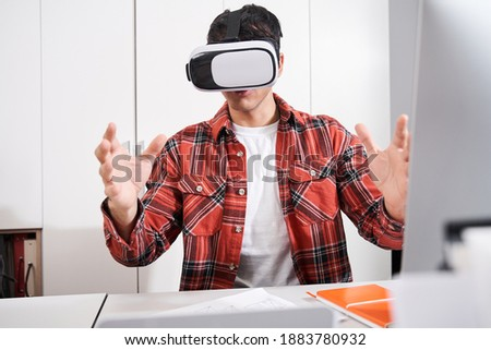 Waist up portrait of the male graphic designer in virtual reality headset using new technologies while working in modern office. Stock photo