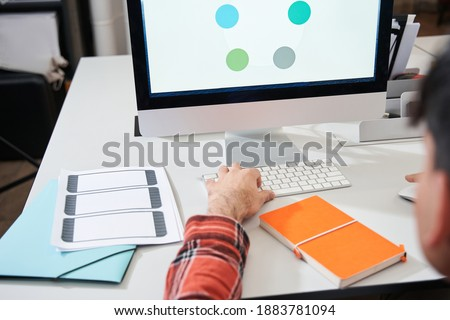 Cropped view of the male graphic designer or illustrator working in creative office while sitting in front of the imac computer. Stock photo