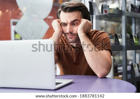 Portrait view of the serious bored man using laptop in cafe while waiting for his coffee. Man sitting at a cafe and looking at the laptop screen