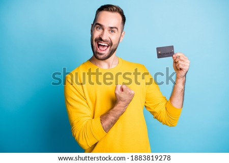 Photo of young excited happy positive cheerful smiling man hold credit card raise fist in victory isolated on blue color background