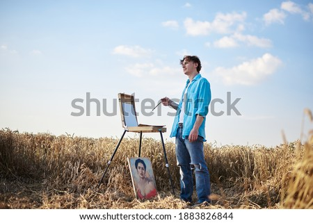 Full-length portrait of young male artist wearing blue shirt, drawing on canvas on easel on wheat field. Painting workshop in rural countryside. Artistic education concept. Outdoors leisure activities