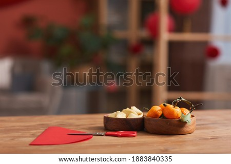 Conceptual no people shot of tangerines, fortune cookies and colored paper on table in living room decorated for Chinese New Year Celebration Royalty-Free Stock Photo #1883840335
