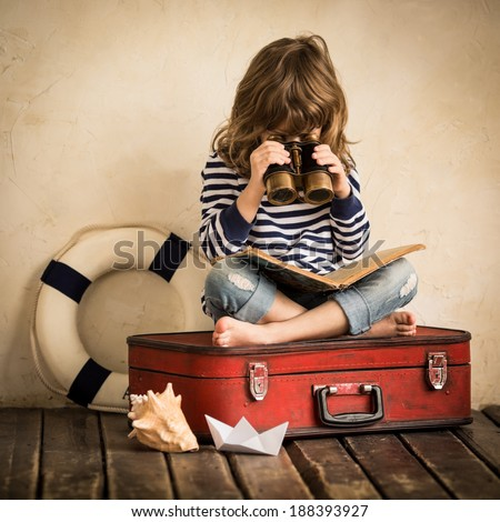 Happy kid playing with toy sailing boat indoors. Child with spyglass reading book. Travel and adventure concept #188393927