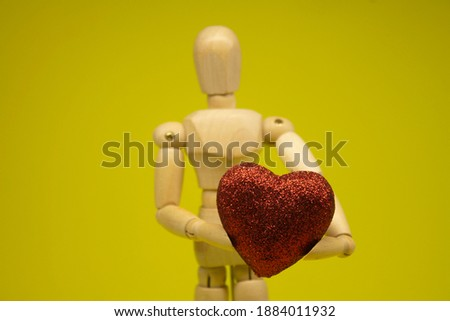 Love and relationship concept, wooden mannequin holding a red heart. Place for text.