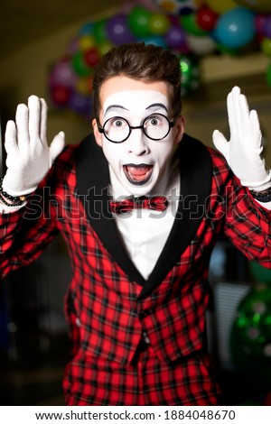 mime guy shows amazing emotions. artist with make-up in glasses and a checkered red suit. Surprise and delight. Holiday animator. Humor. Performance. Clown artists