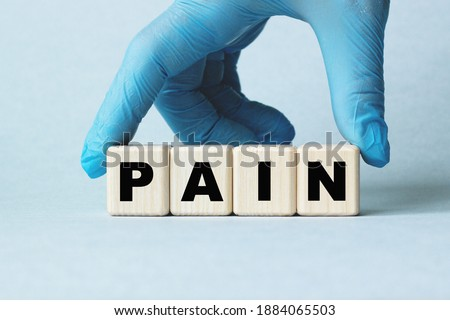 The doctor's hands show the word PAIN . a gloved hand on a white background. Medical concept. the medicine