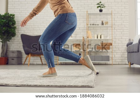 Unrecognizable female trips over rug. Clumsy faceless woman in uncomfortable shoes stumbles on rug in living-room and is about to fall on floor. Domestic accidents and getting injured at home concept Royalty-Free Stock Photo #1884086032