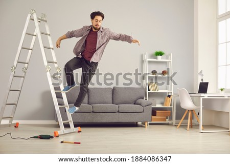 Unlucky young man has slipped from ladder while doing repairs and renovating house and is falling down on floor. Concept of getting hurt and injured in dangerous domestic accidents at home Royalty-Free Stock Photo #1884086347
