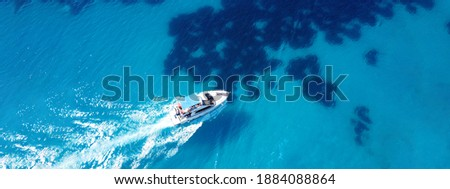 Aerial drone ultra wide photo of tour boat cruising in Caribbean turquoise open ocean sea
