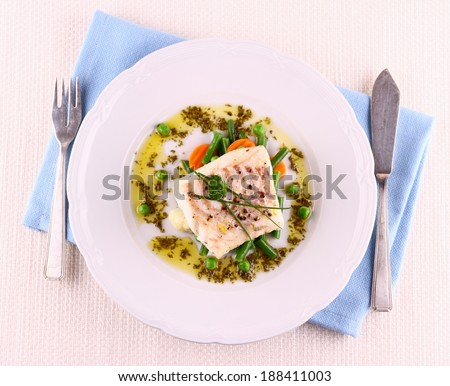 Cod Fillet with green beans, peas, parsley, olive oil, top view