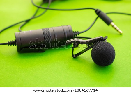 Lavalier or lapel microphone on a colored surface, very close-up. Details of the grip clip or fastener, mic power bank, miniplug, and wind sponge are visible. Concept useful object, sound production,