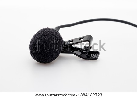 Lavalier or lapel microphone on a surface, very close-up. The details of the grip clip or bra and the sponge against the wind are visible.