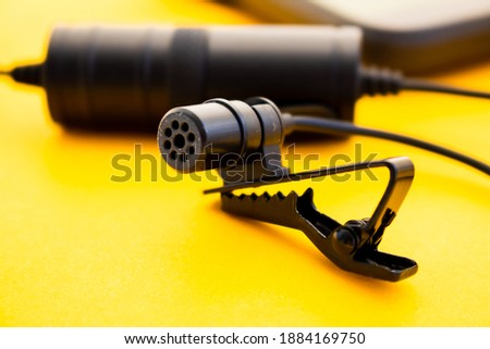 Lavalier or lapel microphone on a colored surface, very close-up. Details of the grip clip or fastener, mic power bank. Concept useful object, sound production,