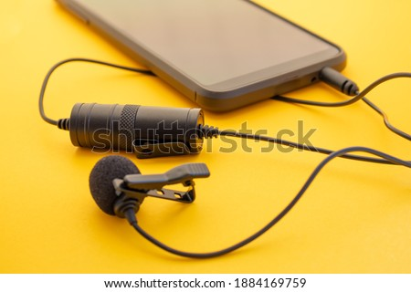 Lavalier or lapel microphone on a colored surface plugged into a cell phone. Details of the grip clip or fastener, mic power bank, miniplug, and wind sponge are visible. Concept useful object
