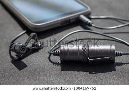 Lavalier or lapel microphone on a black surface, very close-up. The details of the grip clip or bra, , powerbank and conection to cellphone.