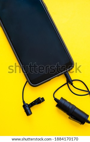 Lavalier or lapel microphone on a yellow surface, very close-up. The details of the grip clip or bra, , powerbank and conection to cellphone.