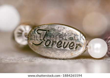Close up shot of a bead with forever text on a bracelet