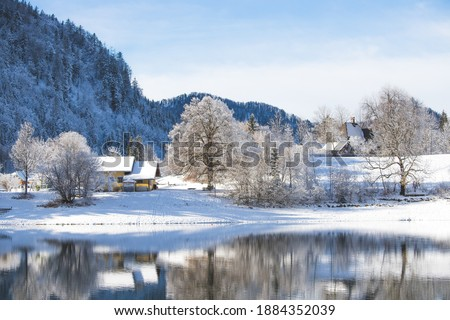 Idyllic winter landscape: Reflection lake, house and snowy trees and mountains Royalty-Free Stock Photo #1884352039