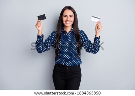 Portrait of pretty content cheerful businesslady holding in hands two bank cards choose isolated over grey pastel color background