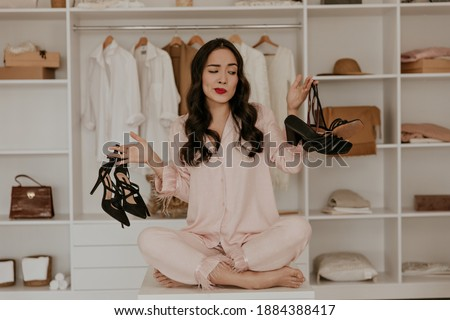 Thoughtful brunette woman in pink pajamas looks at sandals. Lady with red lips poses in dressing room and choose between two pairs of high heels. Royalty-Free Stock Photo #1884388417