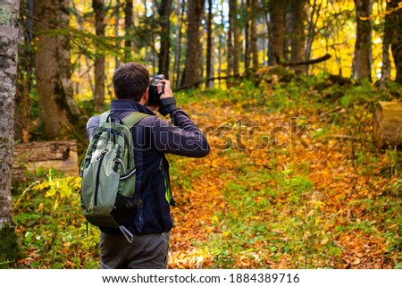 Back view male photographer in bright autumn forest.