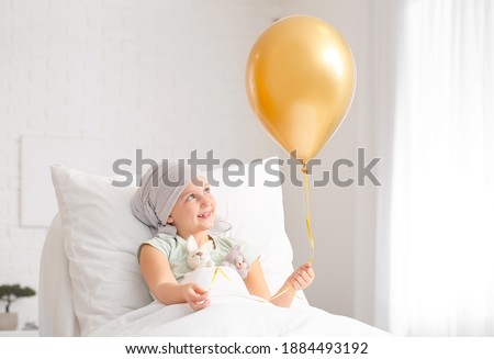 Little girl with golden balloon undergoing course of chemotherapy in clinic. Childhood cancer awareness concept Royalty-Free Stock Photo #1884493192