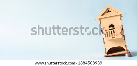 Banner falling miniature wooden house, copy space. House foundation made of coins. Concept of cheap real estate, low interest on mortgages, rental housing
