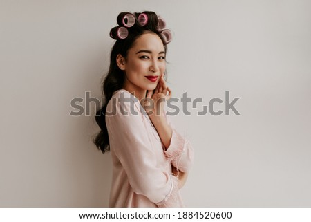 Brown-eyed brunette Asian woman with hair curlers and red lips dressed in stylish pink pajamas smiles and looks into camera on white isolated background.