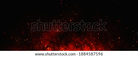 Fire embers particles over black background. Fire sparks background. Abstract dark glitter fire particles lights. bonfire in motion blur. Royalty-Free Stock Photo #1884587596