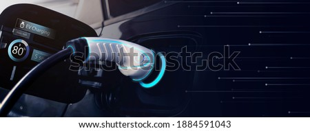 Power cable pump plug in charging power to electric vehicle EV car with modern technology UI control information display, car fueling station connected power cable alternative sustainable eco energy Royalty-Free Stock Photo #1884591043