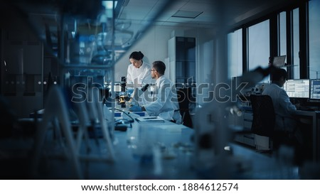 Modern Medical Research Laboratory: Two Scientists Working, Using Digital Tablet, Analyzing Test, Talking. Advanced Scientific Pharmaceutical Lab for Medicine, Biotechnology Development. Evening Time Royalty-Free Stock Photo #1884612574
