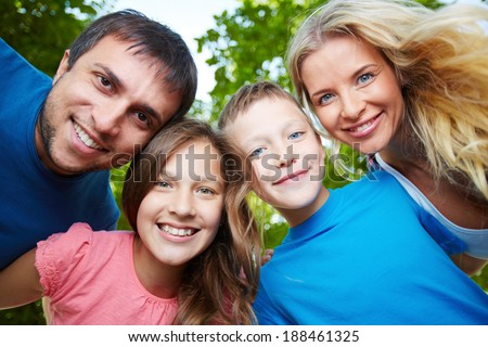 Photo of happy family of four looking at camera outdoors #188461325
