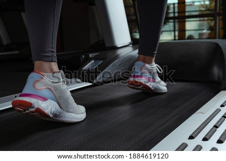 Young beautiful woman on the treadmill in the gym. Close-up shoes appear.