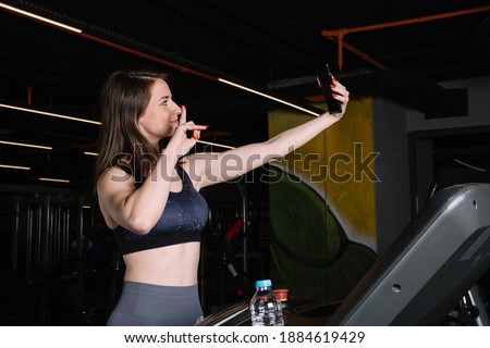 Young beautiful woman doing selfie on the treadmill in the gym. The woman who enjoys doing sports takes selfies.