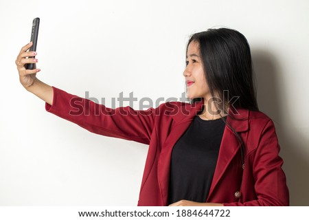 Happy Asian business woman with mobile phone making selfie. Portrait of smiling girl, posing on white background