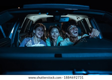 Portrait of three young friends looking emotional, laughing while sitting together in the car and watching a movie in a drive in cinema. Entertainment, leisure activities concept. Horizontal shot Royalty-Free Stock Photo #1884692731