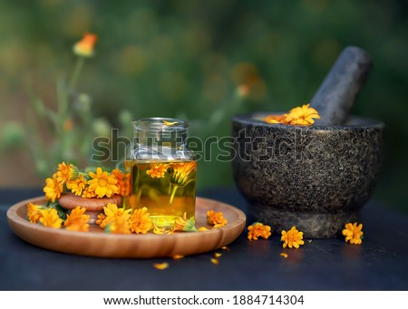 glass bottle essential oil of calendula and fresh calendula flowers leave on a wooden plate and a granite mortar on a black table with a blurred background. Concept: spa, aromatherapy and beauty.