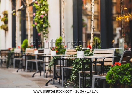 Outdoor empty coffee and restaurant terrace with potted plants tables and chairs in london indie and hipster style Royalty-Free Stock Photo #1884717178