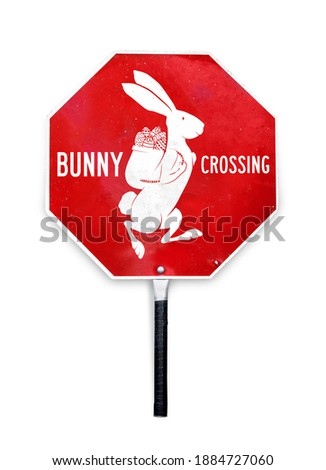 Stop bunny crossing sign. Silhouette of rabbit with basket filled with Easter eggs. Easter themed stop sign used to control traffic. Red and white metal sign in octagon shape and a pole to hold.