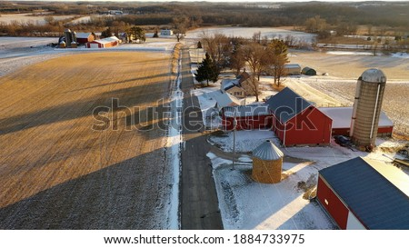 Establishing shot of Midwestern countryside in winter.  Aerial view of  rustic road, farm houses, farms along the street. Agricultural field  covered in first snow, sunny, soft sunlight at sunset  Royalty-Free Stock Photo #1884733975