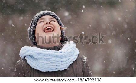 child is catching snowflakes by mouth at winter, portrait of charming girl outdoors
