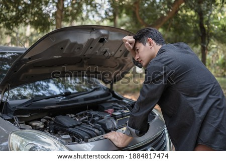 Man' hand open hood of a broken car and wipe the sweat on the road in the forest. Car breakdown concept. Royalty-Free Stock Photo #1884817474