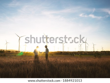 Investors and technician who are out of focus in the foreground are standing in talks about wind turbine power generation, Wind turbine farm is an alternative electricity source for business. Royalty-Free Stock Photo #1884921013