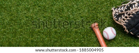 Baseball bat, glove and ball on green grass field.  Sport theme background with copy space for text and advertisment Royalty-Free Stock Photo #1885004905