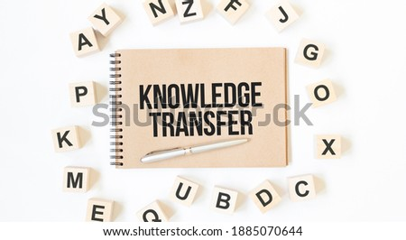 Text KNOWLEDGE TRANSFER on the craft colored notepad with block wood cubes on the white background
