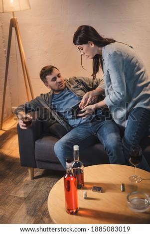 woman showing coins and empty wallet to drunk husband sitting on sofa with glass of whiskey Royalty-Free Stock Photo #1885083019