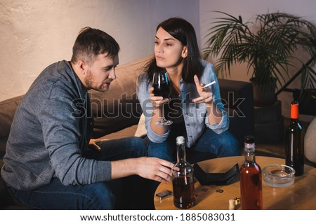 drunk husband and wife sitting at table with bottles and empty wallet Royalty-Free Stock Photo #1885083031