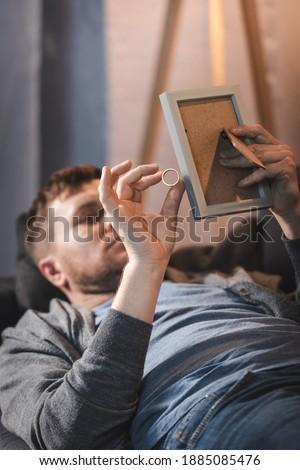 depressed, alcohol-addicted man holding photo frame and wedding ring while lying on sofa
