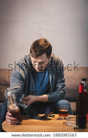 frustrated, addicted man holding bottle of whiskey near empty wallet on table Royalty-Free Stock Photo #1885085563